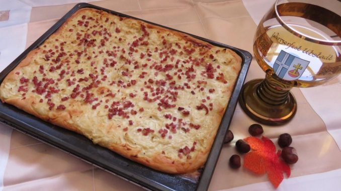 Zwiebelkuchen und neuer Wein angerichtet. Foto: HV
